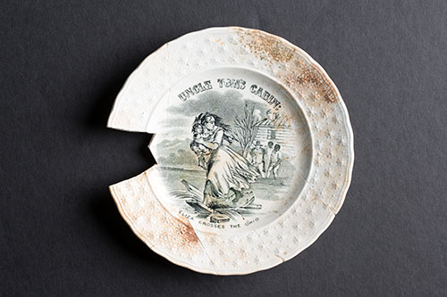 A simple plate adorned with a scene from Uncle Tom's Cabin