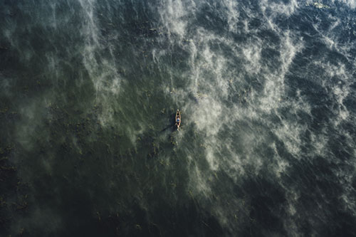 Aerial shot of someone canoeing on a lake
