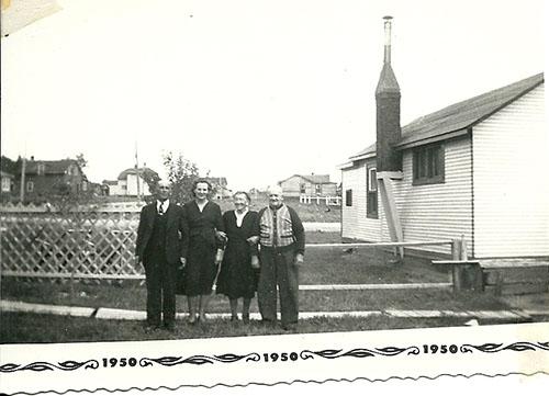 Quatre personnes debout devant un vieux bâtiment