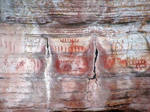 Un panneau de la longue série de pictogrammes au site de la rivière Nipigon. L'image au centre montre distinctement celle d'un grand canot.